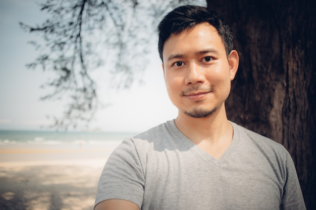 Cerca del hombre está de pie bajo el árbol de pino en la playa.