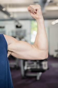 Cerca del hombre que muestra bíceps en el gimnasio