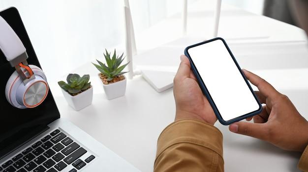 Cerca de un hombre que sostiene un teléfono inteligente en la mano en el lugar de trabajo con una computadora portátil y un enrutador inalámbrico.