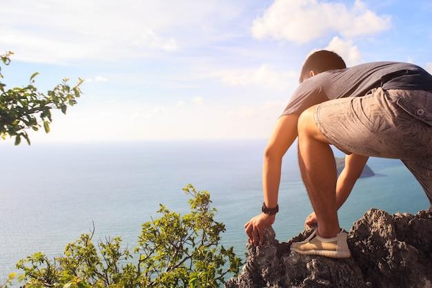 Cerca del hombre que sube a la cima de la montaña