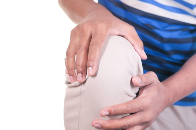 Cerca del hombre que sufre dolor en las articulaciones de la rodilla aislado en blanco