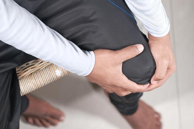 Cerca del hombre que sufre dolor en las articulaciones de la rodilla de arriba hacia abajo