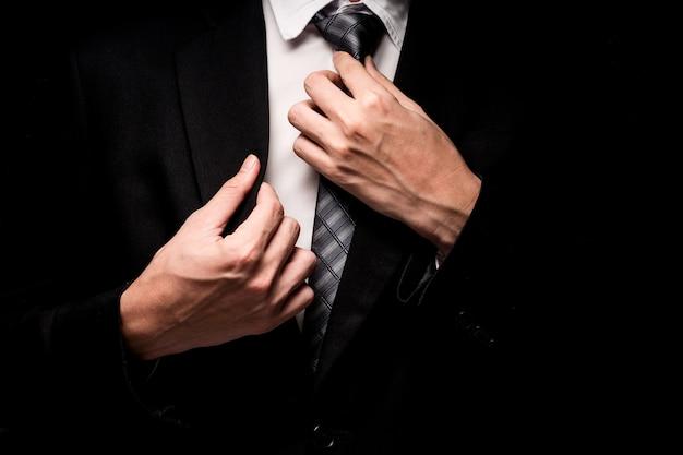 Cerca del hombre en traje negro, camisa y corbata sobre fondo negro