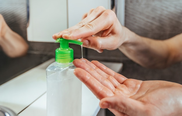 De cerca. hombre usando un dispensador con jabón bactericida. concepto de prevención de enfermedades infecciosas.