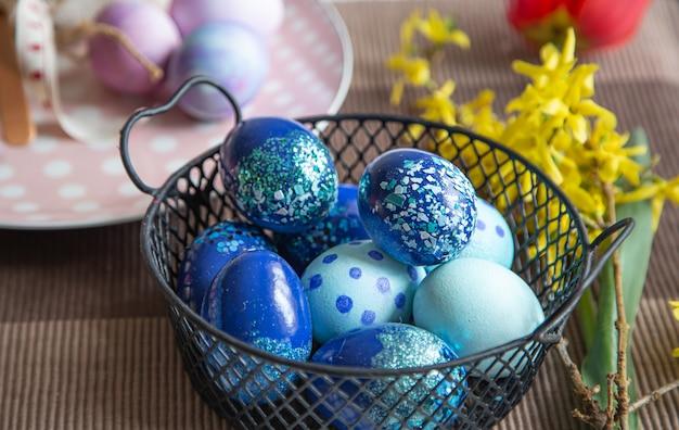 Cerca de huevos de pascua decorados en una canasta de metal. concepto de vacaciones de semana santa e ideas para la decoración.