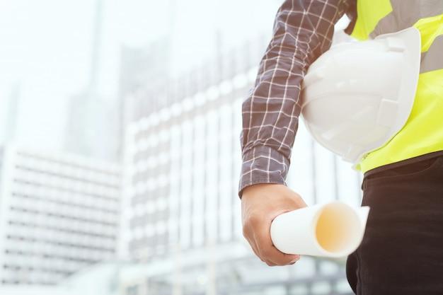 Cerca de la ingeniería masculina trabajador de la construcción con papel de rollo