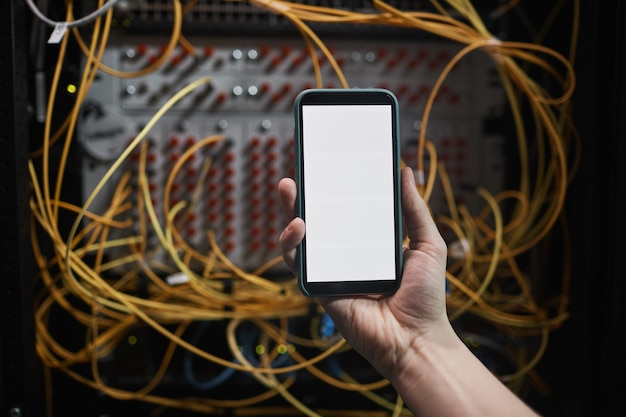 Cerca del ingeniero de redes sosteniendo un teléfono inteligente con pantalla en blanco en la sala de servidores durante los trabajos de mantenimiento en el centro de datos, espacio de copia