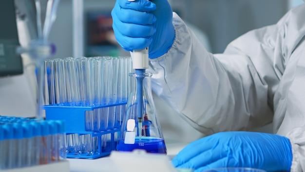 Cerca del investigador que prueba la muestra líquida con una micropipeta para un nuevo tratamiento de laboratorio médico. equipo de médicos que examinan la evolución del virus utilizando alta tecnología para el desarrollo de vacunas contra covid19