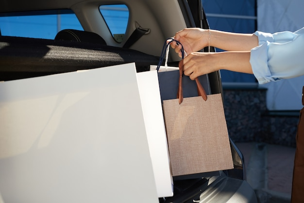 Cerca de irreconocible joven cargando bolsas de compras en el maletero del coche en el estacionamiento por centro comercial, espacio de copia