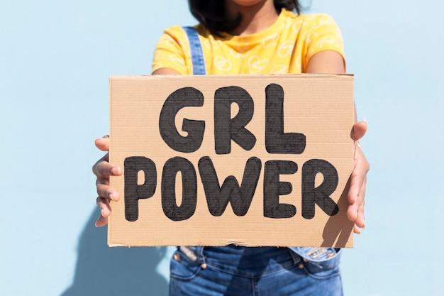 Cerca de irreconocible mujer sosteniendo una pancarta con el lema girl power