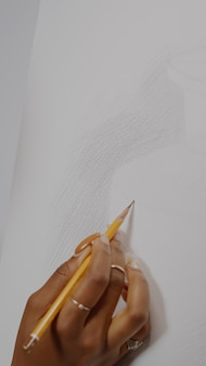 Cerca del jarrón de dibujo sobre lienzo blanco y mano negra