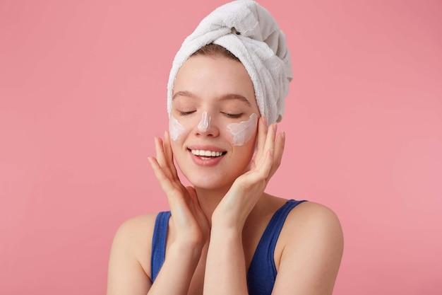 Cerca de joven agradable mujer alegre con belleza natural con una toalla en la cabeza después de la ducha, se pone de pie y se pone crema facial con los ojos cerrados.