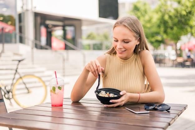 Cerca de joven atractiva comiendo ensalada en el café de la calle