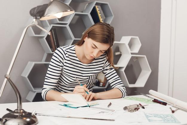 Cerca de la joven y atractiva diseñadora independiente europea con cabello oscuro en ropa de rayas sentado a la mesa en la oficina, anotando los errores del proyecto en el cuaderno para discutirlos en la reunión.