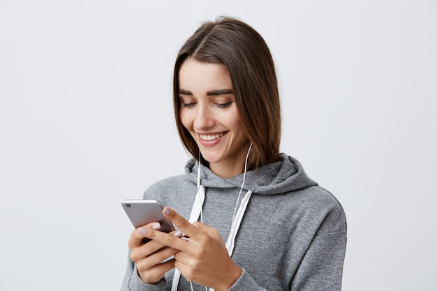Cerca de la joven y atractiva estudiante caucásica feliz con el pelo largo y oscuro en gris con capucha riendo, mirando el video divertido de la fiesta en el teléfono, escuchando su canción favorita con auriculares.