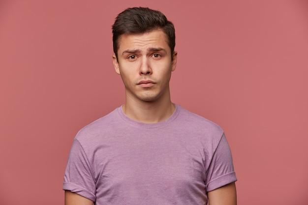 Cerca de joven atractivo ofendido en camiseta en blanco, se encuentra sobre fondo rosa y se ve triste e infeliz.