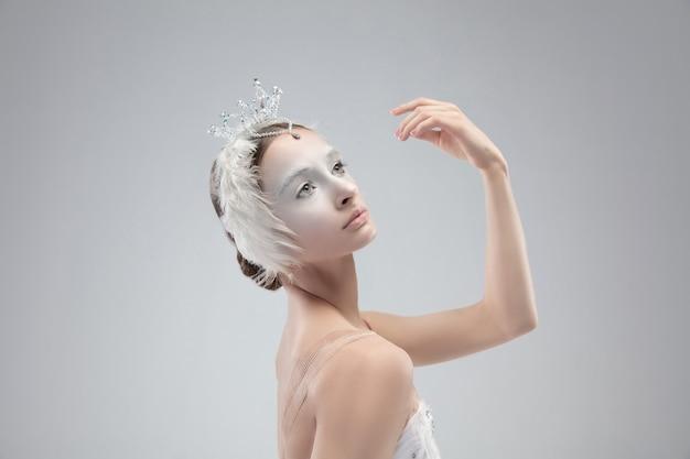 Cerca de la joven bailarina agraciada sobre fondo blanco de estudio
