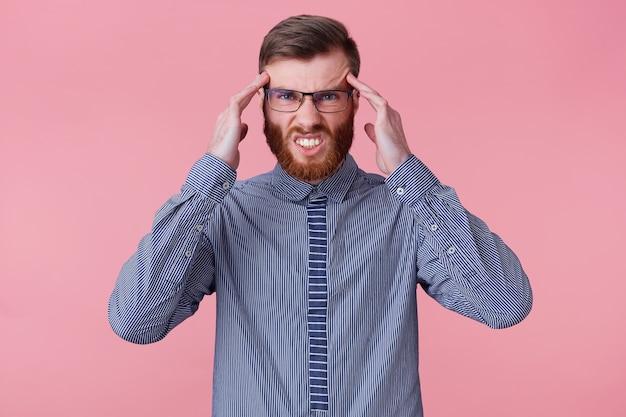 Cerca de joven barbudo, con un dedo en la sien, difícil de pensar y tratar de resolver un problema grave, retorciéndose de dolor aislado sobre fondo rosa.