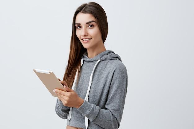 Cerca de la joven y bella muchacha alegre caucásica con cabello largo y oscuro en traje deportivo casual sonriendo brillantemente chateando con amigos en tableta digital
