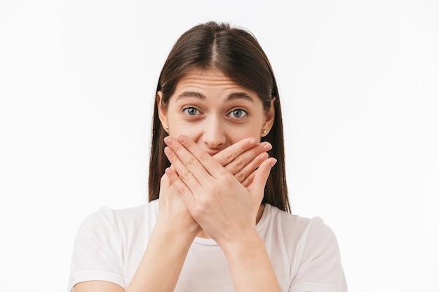 Cerca de una joven bella mujer aislada, cubrir la boca con las manos