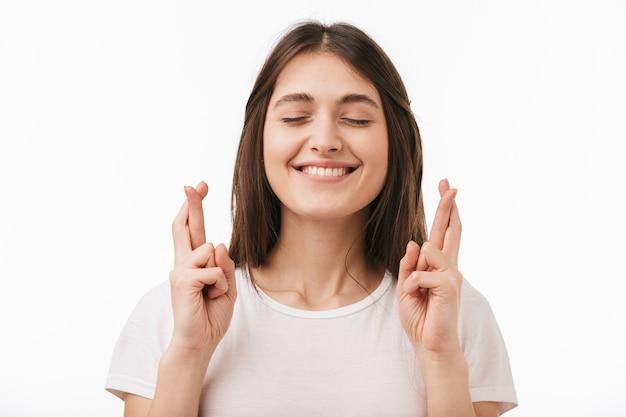 Cerca de una joven y bella mujer aislada, sosteniendo los dedos cruzados para la buena suerte