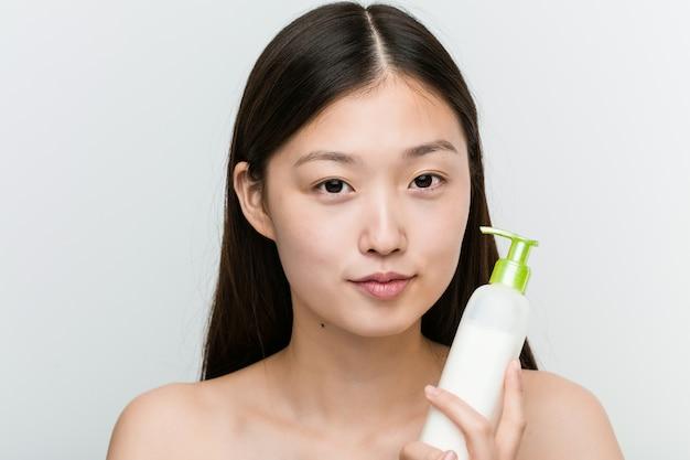 Cerca de una joven bella y natural mujer asiática sosteniendo una botella de crema hidratante