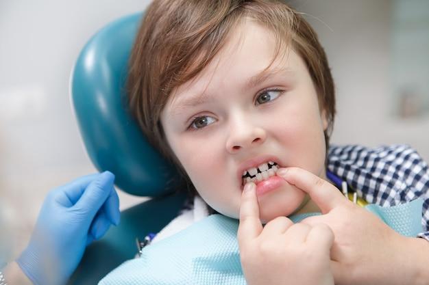 Cerca de un joven divertido mostrando sus dientes al dentista