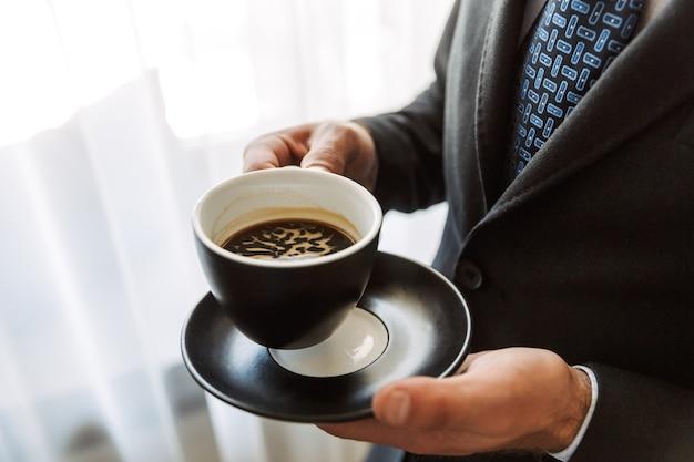 Cerca de un joven empresario vistiendo traje de pie en la habitación del hotel, sosteniendo una taza de café