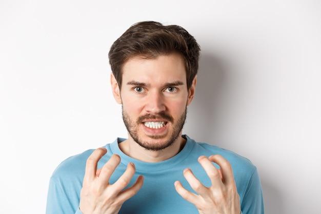 Cerca de un joven enojado con barba, un apretón de manos enojado, apretar los dientes y fruncir el ceño furioso, de pie indignado sobre el fondo blanco.