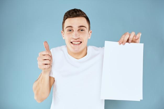Cerca de joven feliz en camiseta blanca sosteniendo una hoja de papel en blanco