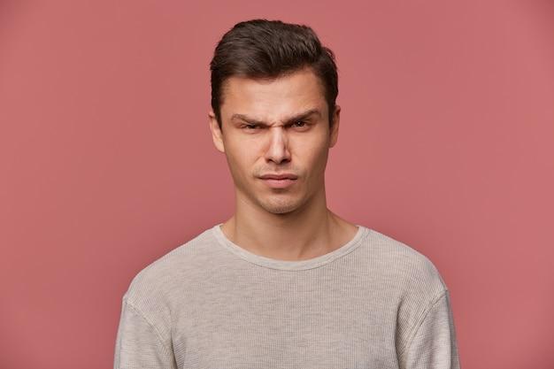Cerca de joven guapo estricto viste en manga larga básica, mira a la cámara con expresión enojada, aislada sobre fondo rosa.