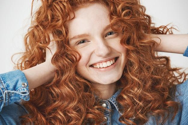Cerca de joven hermosa chica jengibre tocando el cabello sonriendo