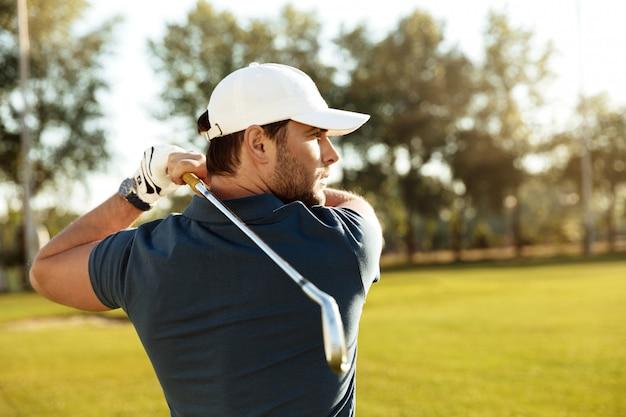 Cerca de un joven hombre concentrado disparando una pelota de golf