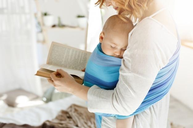 Cerca de la joven madre leyendo cuentos de hadas para su pequeño hijo recién nacido en la cómoda habitación de luz. el bebé se duerme mientras leía.