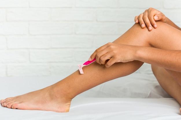 Cerca de una joven mujer afroamericana afeitarse las piernas