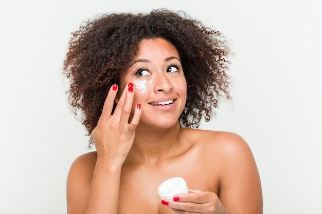 Cerca de una joven mujer afroamericana aplicando una crema hidratante