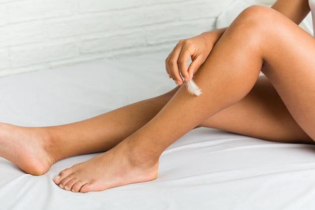 Cerca de una joven mujer afroamericana cuidando la piel de sus piernas