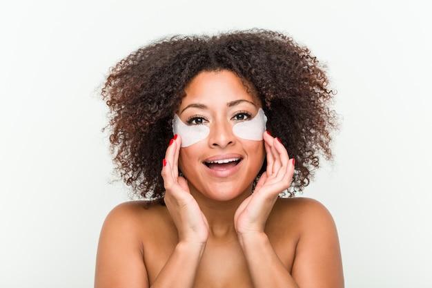 Cerca de una joven mujer afroamericana con un tratamiento para la piel de los ojos