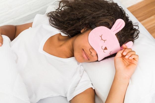 Cerca de una joven mujer cansada afroamericana durmiendo en la cama