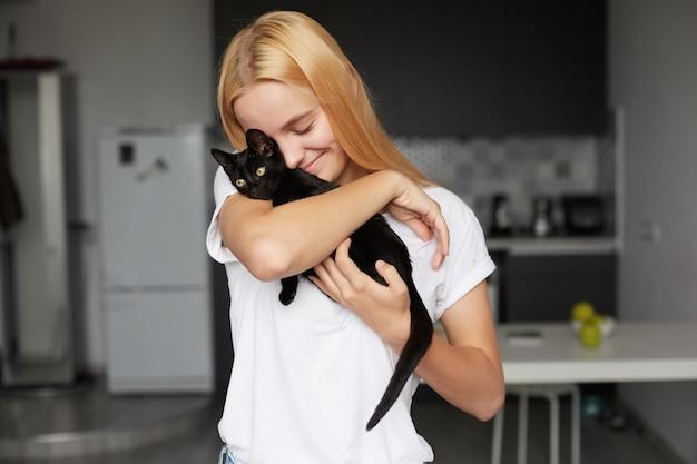 Cerca de la joven mujer rubia en la cocina tiene en las manos un pequeño gatito negro