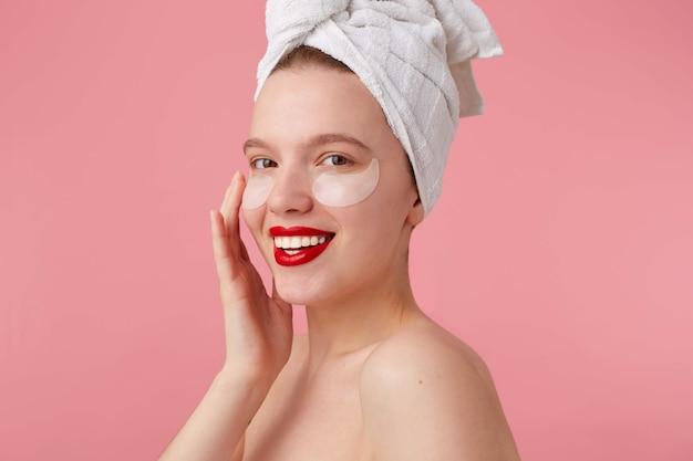 Cerca de la joven mujer sonriente con una toalla en la cabeza después de la ducha, con parches y labios rojos, toca la cara y se ve feliz, se levanta.
