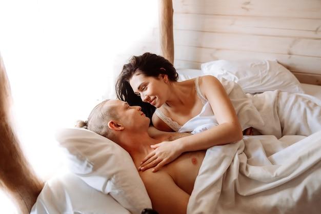 Cerca de joven y mujer tomando el sol en la cama juntos
