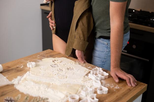 Cerca de la joven pareja manos cocinando en la cocina