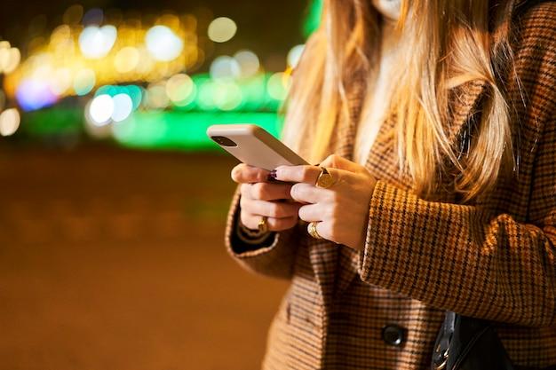 Cerca de una joven rubia con un teléfono inteligente, escribiendo un mensaje, en una ciudad de noche, con luces de fondo y tráfico.