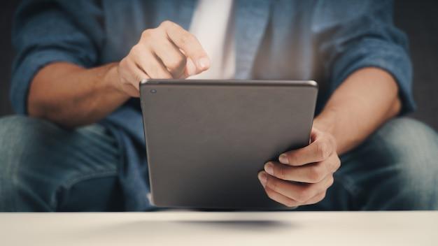 Cerca de joven con tableta en el sofá. buscar, navegar, hacer compras en línea, redes sociales.