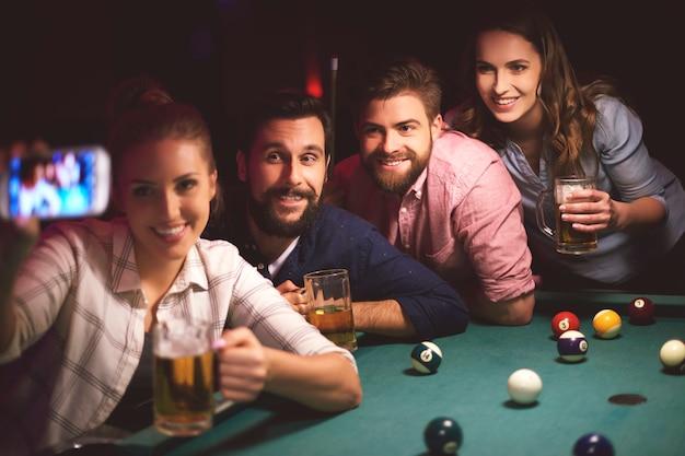 Cerca de jóvenes amigos que se divierten jugando al billar