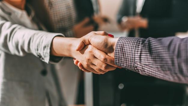 Cerca de jóvenes empresarios casuales dándose la mano con cada uno