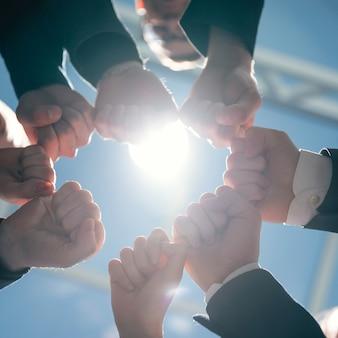De cerca. jóvenes empresarios mostrando su unidad. concepto de trabajo en equipo.