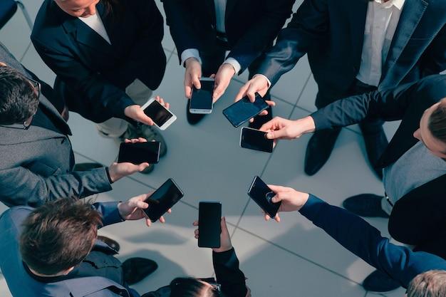 Cerca de jóvenes empresarios con teléfonos inteligentes de pie en círculo