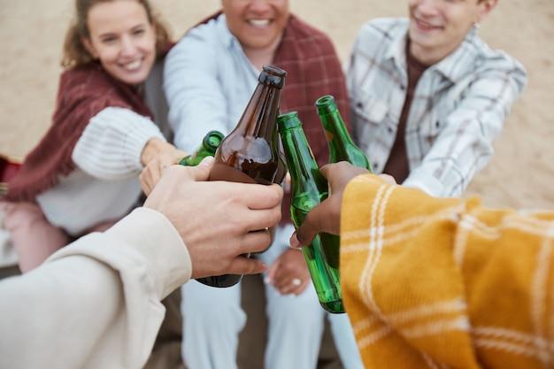 Cerca de jóvenes tintineo de botellas de cerveza mientras disfrutan de acampar en la playa en otoño